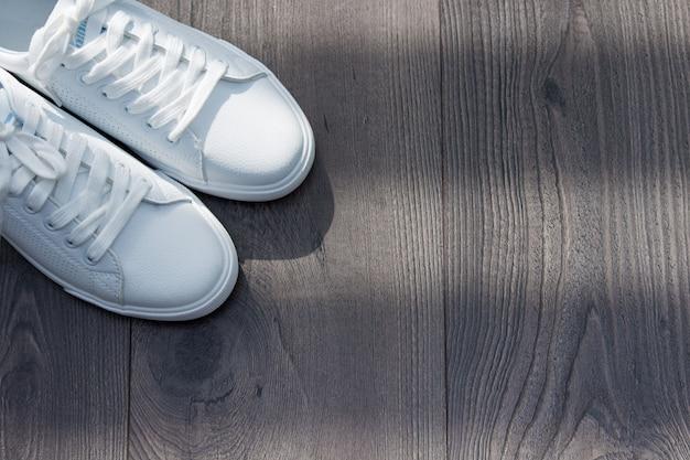 Sapatas fêmeas das sapatilhas do couro branco em laços no fundo de madeira marrom cinzento.