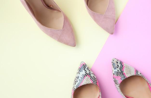 Sapatas fêmeas pálidas do rosa e da cópia da serpente sapatas do salto alto da mulher no fundo bege e cor-de-rosa.