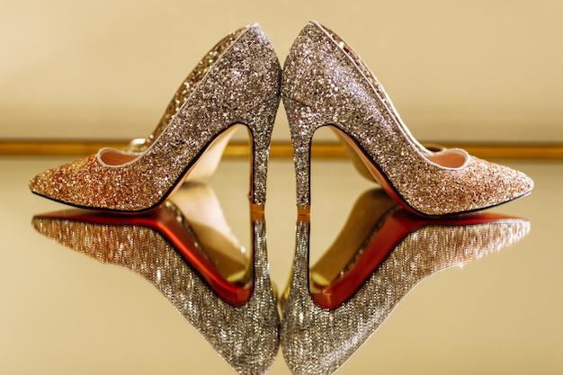 Sapatas luxuosas elegantes em uma tabela do espelho, foco seletivo do casamento.