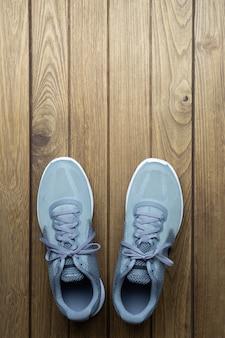 Sapatas running do esporte na opinião superior do fundo de madeira com espaço da cópia.