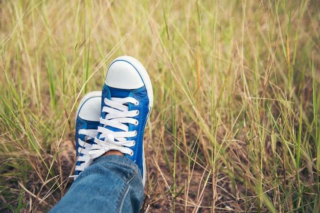 Sapatilha azul, jeans bonito do desgaste de mulher e uma sapatilha azul em um prado verde.