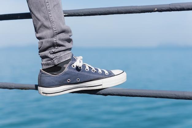 Sapatilha azul na perna da menina em brim sobre o mar verde