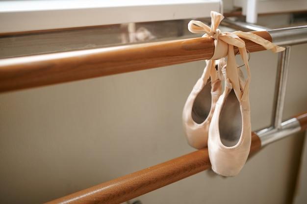 Sapatilha de balé rosa com fita pendurada na barra na aula de dança