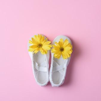 Sapatilhas brancas com flores amarelas em um fundo rosa