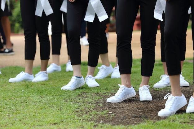 Sapatilhas brancas de muitas mulheres no chão de grama