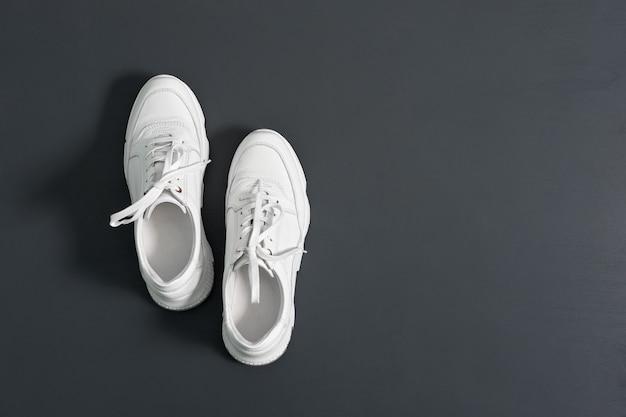 Sapatilhas de couro modernas brancas da juventude para mulheres no fundo cinzento da parede. copie o espaço.