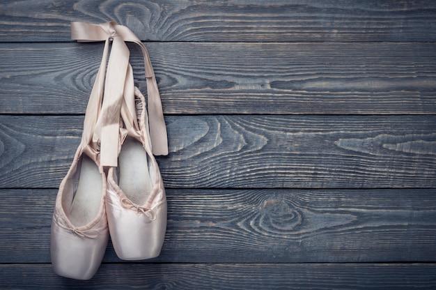 Sapatilhas de dança de balé com um laço de fitas pendurar um prego na madeira