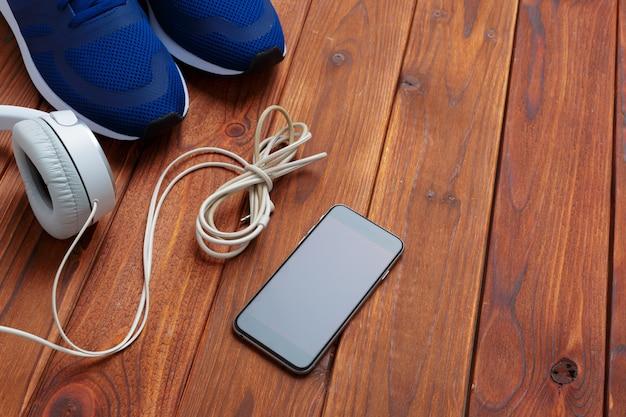 Sapatilhas e celular com fones de ouvido na mesa de madeira