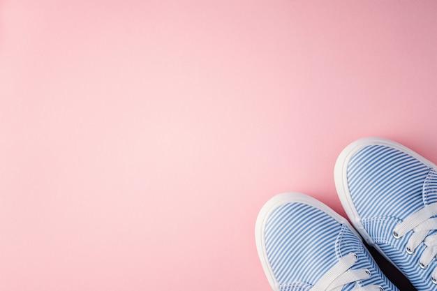 Sapatilhas fêmeas com laços no fundo cor-de-rosa com espaço da cópia.