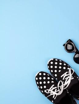 Sapatilhas fêmeas e óculos de sol com espaço da cópia.