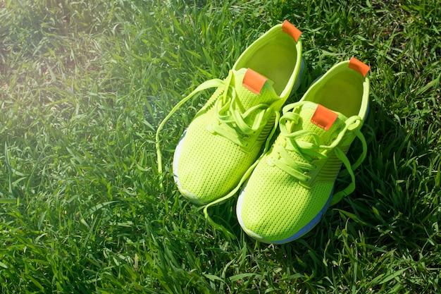 Sapatilhas verdes brilhantes na grama