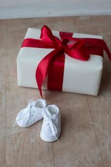 Sapatinhos de bebê branco, caixa de presente, fotos de maternidade. conceito de gravidez feliz