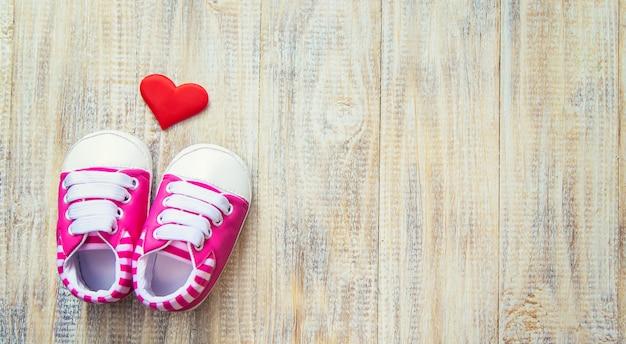 Sapatinhos de bebê e coração em uma luz.