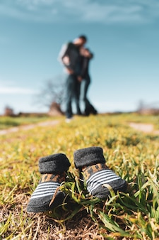 Sapatinhos de bebê na grama com uma mulher grávida e o marido ao fundo