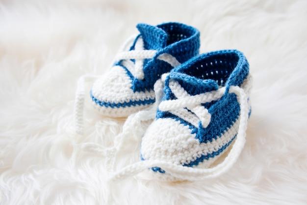 Sapatinhos de bebê. primeiros tênis feitos à mão para menino ou menina recém-nascido.