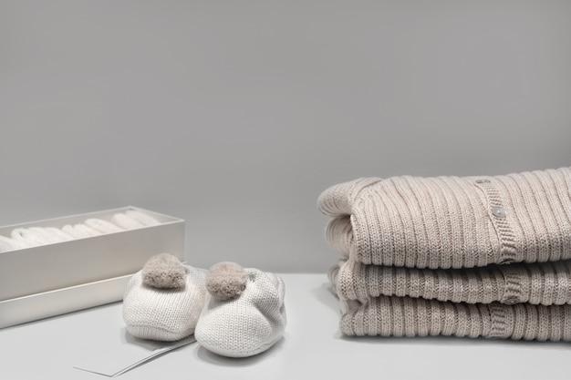 Sapatinhos de bebê, suéteres e meias feitas de tecidos bege naturais estão sobre a mesa.