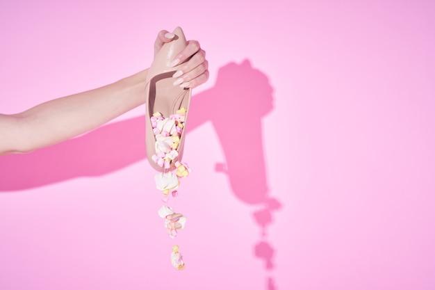 Sapato com decoração decoração fundo rosa mão feminina