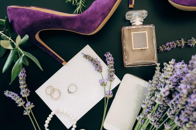 Sapato de salto alto lilás um frasco de perfume uma joia para smartphone e flores em uma superfície verde
