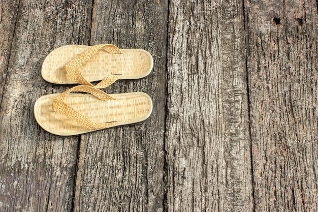 Sapato tecer, em frente ao quarto de hotel sobre a textura de madeira antiga.