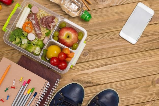Sapatos azuis, cadernos com canetas e bacon e lancheira de vegetais