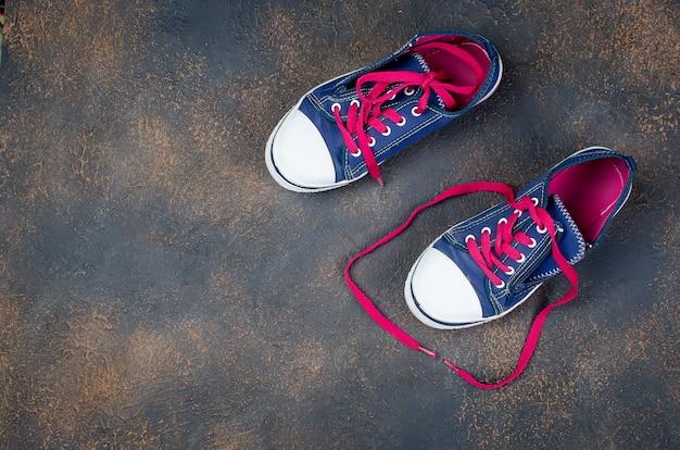 Sapatos azuis esportes com cadarços rosa no chão