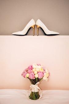 Sapatos brancos e um buquê. buquê de casamento com peônias brancas e rosa.