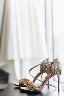 Sapatos brilhantes ricos com cristais estão diante de um vestido pendurado