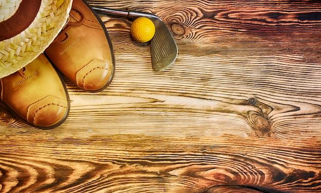 Sapatos, chapéu de palha, bola de golfe no fundo de madeira