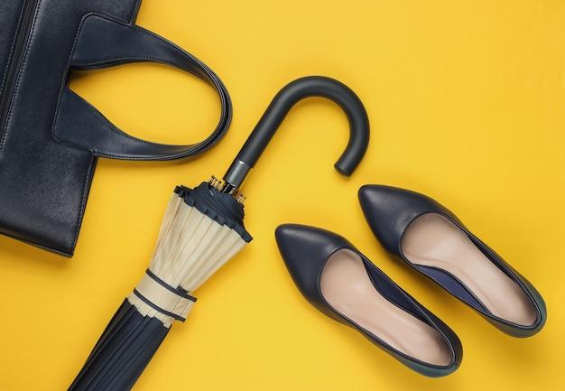 Sapatos clássicos de salto alto, bolsa de couro, guarda-chuva amarelo