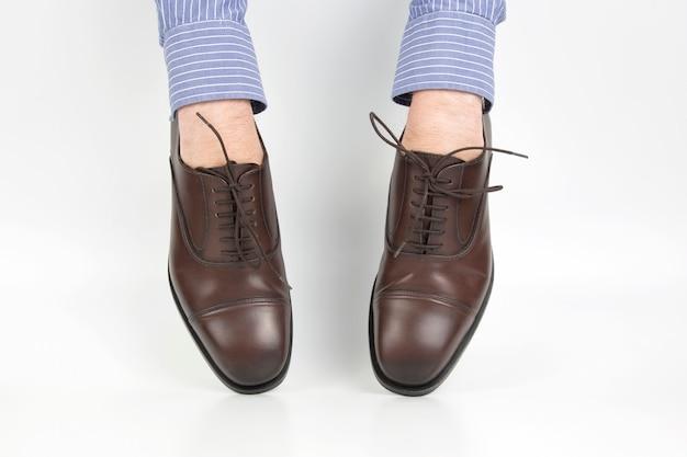 Sapatos clássicos usados nas mãos em um fundo branco
