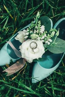 Sapatos com flores e anéis na grama