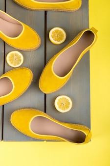 Sapatos de alpercatas amarelas perto de fatias de limão