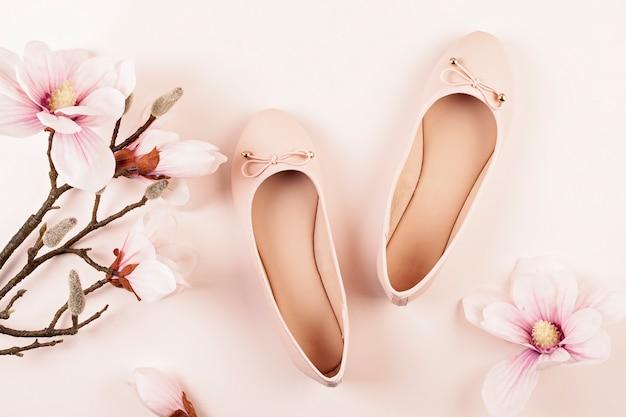 Sapatos de bailarina de cor nude e flores de magnólia.