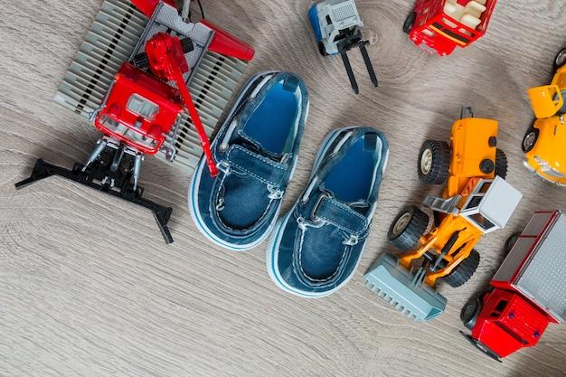 Sapatos de barco azul para menino perto de um conjunto de brinquedo de carro em fundo cinza de madeira. vista do topo. quadro, armação. copie o espaço.