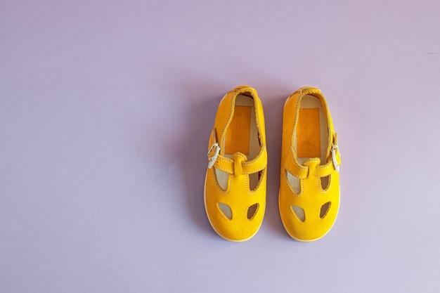 Sapatos de bebê amarelos brilhantes em um lilás