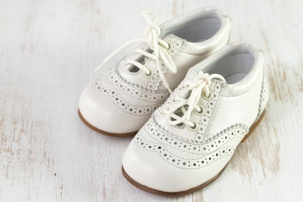 Sapatos de bebê branco em branco de madeira