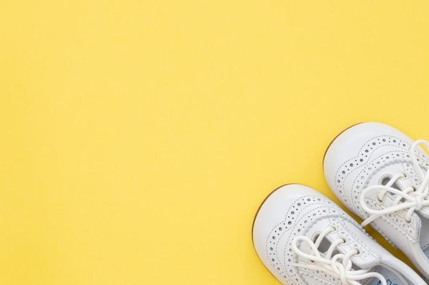 Sapatos de bebê brancos em fundo amarelo