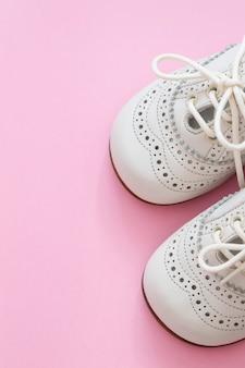 Sapatos de bebê brancos em fundo rosa