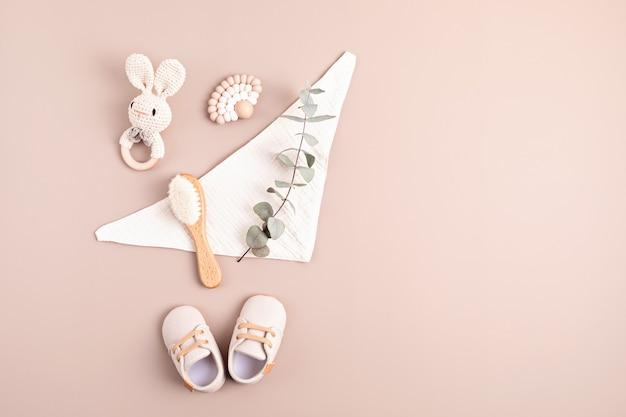 Sapatos de bebê chocalham e mordem em fundo neutro. presentes orgânicos recém-nascidos com a marca da ideia de empresa de pequeno porte. cartão de convite do chá de bebê. vista superior plana