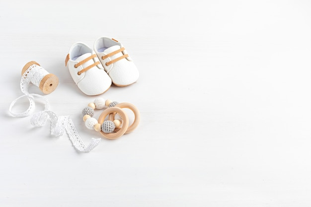Sapatos de bebê e acessórios neutros em termos de gênero. moda recém-nascida orgânica, identidade visual, ideia de empresa de pequeno porte. chá de bebê, convite de batismo, cartão de felicitações. camada plana, vista superior