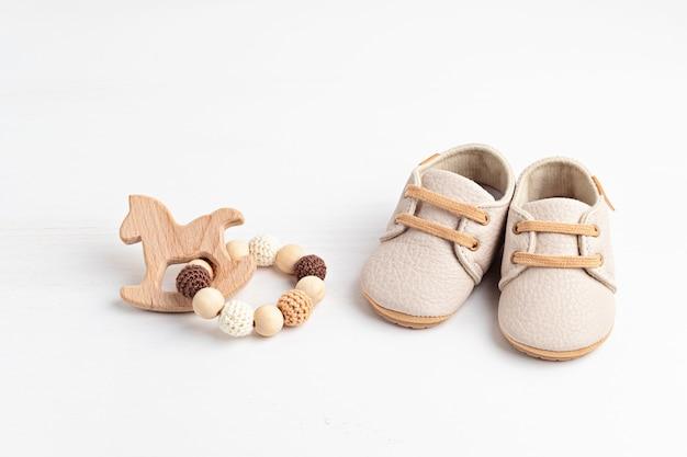Sapatos de bebê e acessórios neutros em termos de gênero. moda recém-nascida orgânica, identidade visual, ideia de empresa de pequeno porte. convite do chá de bebê, cartão de felicitações. camada plana, vista superior