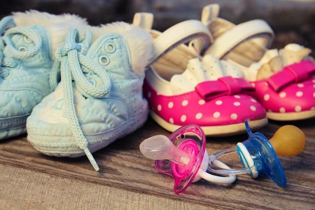 Sapatos de bebê e chupetas rosa e azul