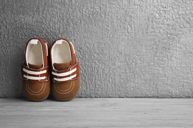 Sapatos de bebê marrons na parede texturizada cinza