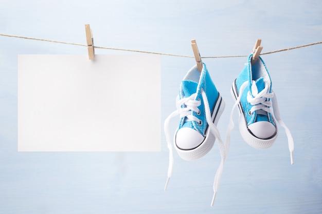 Sapatos de bebê minúsculo bonito em um fundo de madeira com espaço para texto
