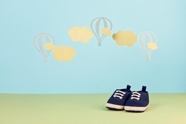 Sapatos de bebé pequeno bonito sobre o fundo azul