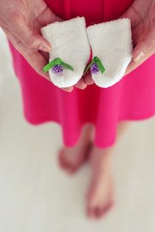 Sapatos de bebê recém-nascido nas mãos das mães, feriado do chuveiro de bebê