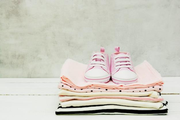Sapatos de bebê rosa menina e roupas recém-nascidas. conceito de maternidade, educação ou gravidez com espaço de cópia.