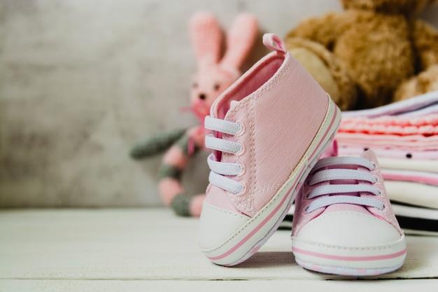 Sapatos de bebê rosa menina, roupas para recém-nascidos e brinquedos macios. conceito de maternidade, educação ou gravidez com espaço de cópia.