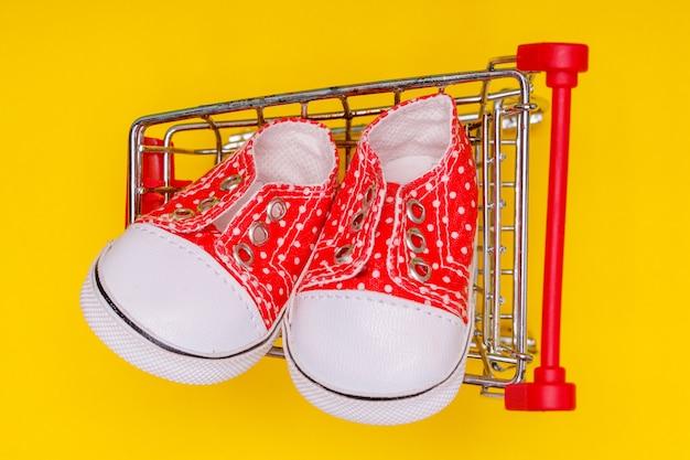 Sapatos de bebê vermelhos com bolinhas brancas em um carrinho de supermercado em um fundo amarelo