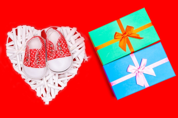 Sapatos de bebê vermelhos com bolinhas brancas em um fundo vermelho com presentes